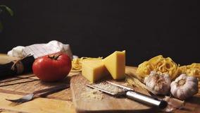 Formaggio tagliuzzato con basilico fresco e spaghetti italiani sul tavolo da cucina di legno stock footage