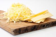 Formaggio tagliuzzato sul bordo di legno della cucina Fotografie Stock Libere da Diritti