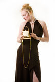Formal attire. Full body of an attractive woman with hair in bun wearing a long formal black gown holding a little gold purse Stock Image