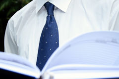 Formal attire. Man in white shirt and blue tie reading a book stock photo