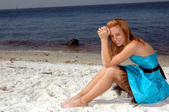 Formal on the beach. A pretty teen sitting in the sand on the beach in a formal dress Stock Photography