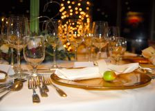 Formal Christmas Dinner Setting. A gold charger, with silverware, napkins, and lots of wine glasses Royalty Free Stock Photos
