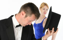 Formal Couple. Focus on woman.  Beautiful young woman in blue formal looking at camera behind attractive young man in tux Stock Images