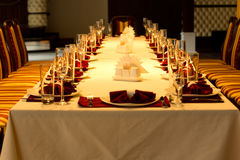Formal dinner table settings for a special event. View down the length of a long formal dinner table with red accented place settings with linen, elegant Stock Images