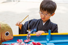 Formal Fishing for Five-Year-Old. A boy in a black kimono hooks a decorative fish at a Japanese shrine during the 7-5-3 Ceremony Royalty Free Stock Images