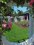 Formal garden. Seen through the decorated window, foreground blurry Royalty Free Stock Photo