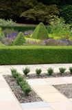 Formal Garden. A portrait format image of a section of formal garden with shaped greenery and bushes / topiary, with a formal layout of pavings stones to the Royalty Free Stock Photography