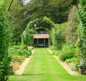 Formal garden with arches. A formal garden design with arches and a grass path leading to a sheltered seating area Royalty Free Stock Photos
