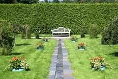 Formal Garden Bench. A wooden bench in a formal garden or park Royalty Free Stock Photography
