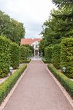 Garden at the Oliwa Park. Formal garden and building at the Oliwa Park Park Oliwski. It`s a public park in Gdansk, Poland Stock Photo