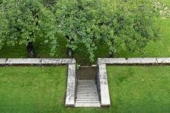 Formal garden design, stone stair in the lawn leads down to the. Formal garden design, old stone stair in the lawn leads down to the orchard, areal view from stock photos