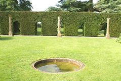 Formal garden with Elizabethan columns, sculptured hedge, & fountain in England, Europe. Stock Images