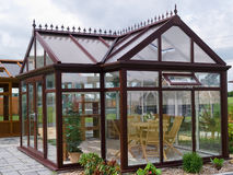 Formal garden glass pavilion with furniture. Formal garden glass metal pavilion with wooden deck and furniture Stock Photo