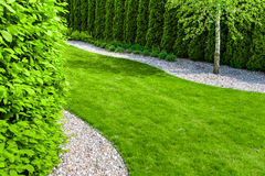 Formal garden with a path of small stones, hedgerow and green lawn Stock Photos