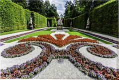 Formal garden with symmetrical flowerbeds. Filled with colorful flowers making a classic pattern with curlicues and gravel pathways between hedges royalty free stock photos
