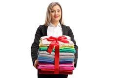Formal gekleidete Frau, die einen Stapel Kleidung eingewickelt mit r hält lizenzfreies stockfoto