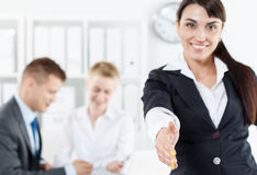 Formal greeting and welcoming gesture. Beautiful smiling business women in suit offering hand to shake while couple employees working in background. Serious Stock Images