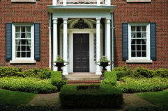 Formal Home Entrance. Red brick house with black shutters and green shrubs with front door flanked by pillars and two flower iron urns; luxury home / house stock image