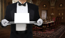 Formal Invitation. Butler in tuxedo tails holding a tray with an invitation on it in a grand, Boroque dining room royalty free stock photos
