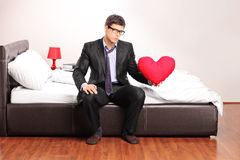 Formal man holding a red heart seated on bed Royalty Free Stock Photo