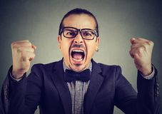 Formal man screaming in anger. Young angry man in eyeglasses shouting expressively looking extremely mad Royalty Free Stock Images