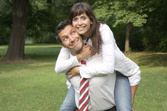 Formal man with tie and woman. Business man holding young girl on back royalty free stock images