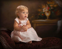 Formal portrait of little girl on small settee. Portrait of little girl in pink Royalty Free Stock Images