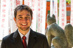 Formal Shrine Visit. A white man, short brown hair, poses in front of a Japanese shrine wearing a suit; big smile Stock Image