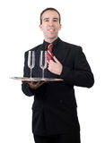 Formal Waiter. A young waiter wearing a suit and carrying away two empty wine glasses, all isolated against a white background Royalty Free Stock Photos