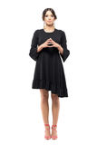 Formal woman in black dress looking at camera with touching fingertips steeple gesture. Full body length portrait isolated on white background stock image