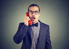 Businessman looking shocked while speaking on phone. Formal young man having breaking news while speaking on phone Royalty Free Stock Photography