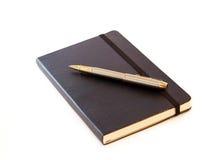 Formale Feder auf einem schwarzen Notizbuch lizenzfreie stockfotos