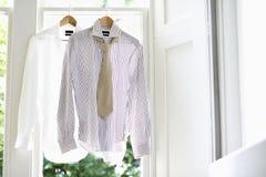 Formale Hemden auf Aufhängern zu Hause Lizenzfreies Stockfoto