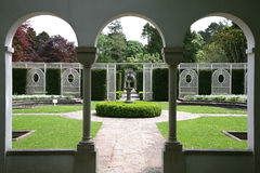 Formaler Garten durch gewölbte Fenster Lizenzfreie Stockfotos