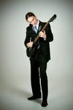 Formaler Mann, der auf Gitarre spielt Stockfotografie