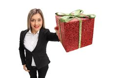 Formally dressed girl showing a gift. Isolated on white background royalty free stock images