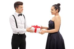 Formally dressed teenage boy giving a gift to his girlfriend. Isolated on white background royalty free stock photo