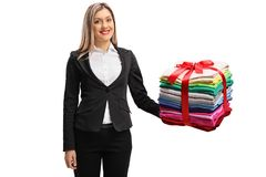 Formally dressed woman holding a stack of ironed and packed clot. Hes wrapped with red ribbon as a gift isolated on white background royalty free stock photo