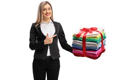 Formally dressed woman holding a stack of packed and ironed clot. Hes wrapped with a ribbon as a gift and pointing isolated on white background stock images