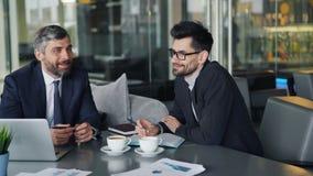 formalwear的快乐的工友经理谈话和微笑在午休时间期间的 股票录像