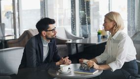 formalwear的成熟买卖人谈话在咖啡馆在工作午餐期间 股票视频