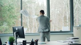 formalwear的无忧无虑的人跳舞在单独工作移动的身体和投掷的纸从表达的书桌兴奋和 股票视频