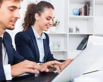 Formalwear de port auxiliaire femelle d'heureuses affaires utilisant l'ordinateur portable image libre de droits