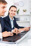Formalwear de port auxiliaire femelle d'heureuses affaires utilisant l'ordinateur portable photo libre de droits