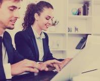 Formalwear de port auxiliaire femelle d'heureuses affaires utilisant l'ordinateur portable Photos stock