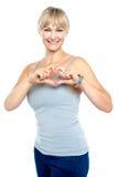 Formar den romantiska en mitt åldras göra en gest hjärta för kvinnan Royaltyfria Bilder
