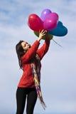 Formar hållande hjärta för den lyckliga härliga flickan ballonger Fotografering för Bildbyråer