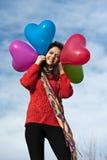 Formar hållande hjärta för den lyckliga härliga flickan ballonger Arkivbild