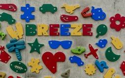 formas 3D e ícones em uma parede, soletrando a brisa da palavra Foto de Stock