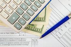 Formas de impuesto con 100 billetes de dólar Imagen de archivo libre de regalías
